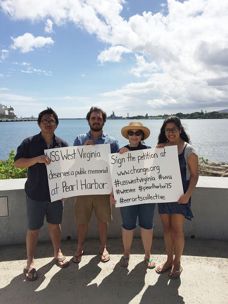 West Virginia University students (from left) Ken Lu, Jared Peterson, Emily Harmon and Tessa Lee Martinez hold up signs for their social media campaign at Pearl Harbor.