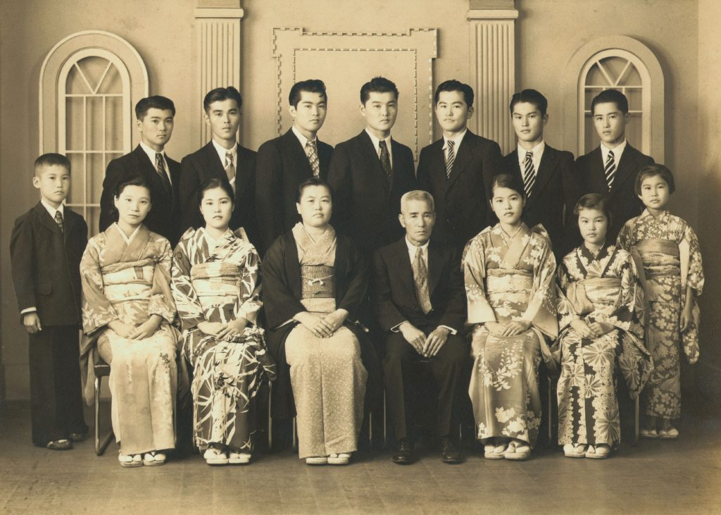 Walter T. Oka is standing at left in this family portrait, taken in 1938. He was 10 at the time. Seated, from left, are his sister-in-law Chieko (Yoshito's wife), sister Itsumi, mother, father, sister Yasue and sister Tomie. Standing, from left, are Walter, brothers Haruto, Yoshito, Shizuo, Toshio, Mitsuo, Kazuyoshi and David and sister Yoshie. Photo courtesy of Walter T. Oka and the Go For Broke National Education Center.